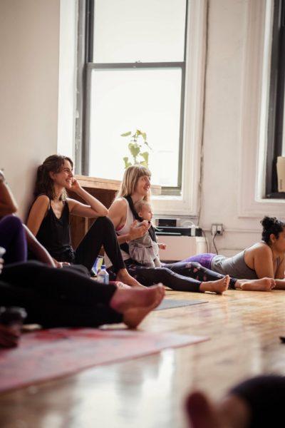 Menschen sitzen im Raum auf dem Boden und hören zu