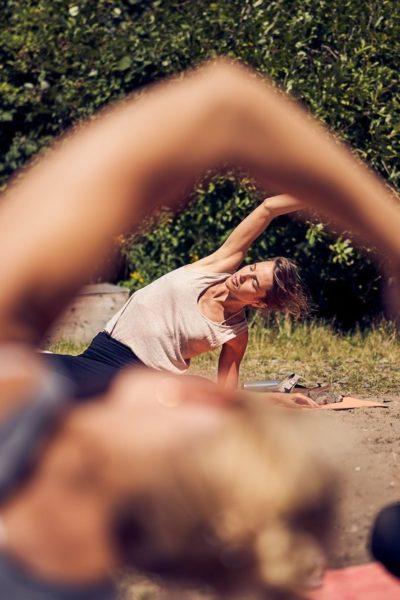 Menschen machen Yoga und lehnen sich sitzend zur linken Seite