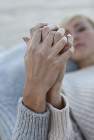 Zwei Frauen halten ihre Hände verschränkt ineinander