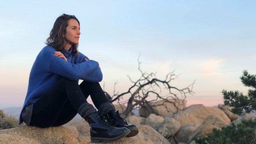 Frau sitzt auf einem Felsen in der Wüste und schaut auf den Sonnenuntergang